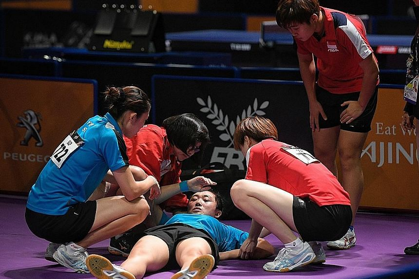 Feng Tianwei receives medical attention after falling and hitting her head during the women's doubles final yesterday. She and Yu Mengyu beat defending champions Zhou Yihan and Lin Ye 11-8, 11-9, 11-13, 8-11, 11-6.