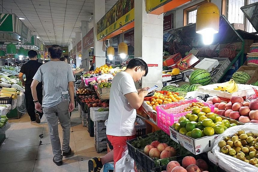 In major Chinese cities, cashless payments - including at hawkers and fruit sellers like this in Beijing - are normal.
