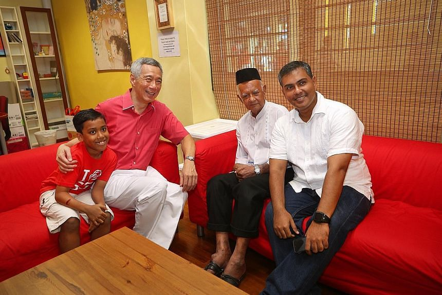 """Prime Minister Lee Hsien Loong with (from left) nine-year-old Adam Zafran Aziz, Mr Ahmad Azali, 79, and Mr Aziz Ahmad, 42. Mr Lee said: """"This is the Singapore of the last half century: Ahmad, a gardener; Aziz, a pharmaceu- tical engineer; and Adam, ("""