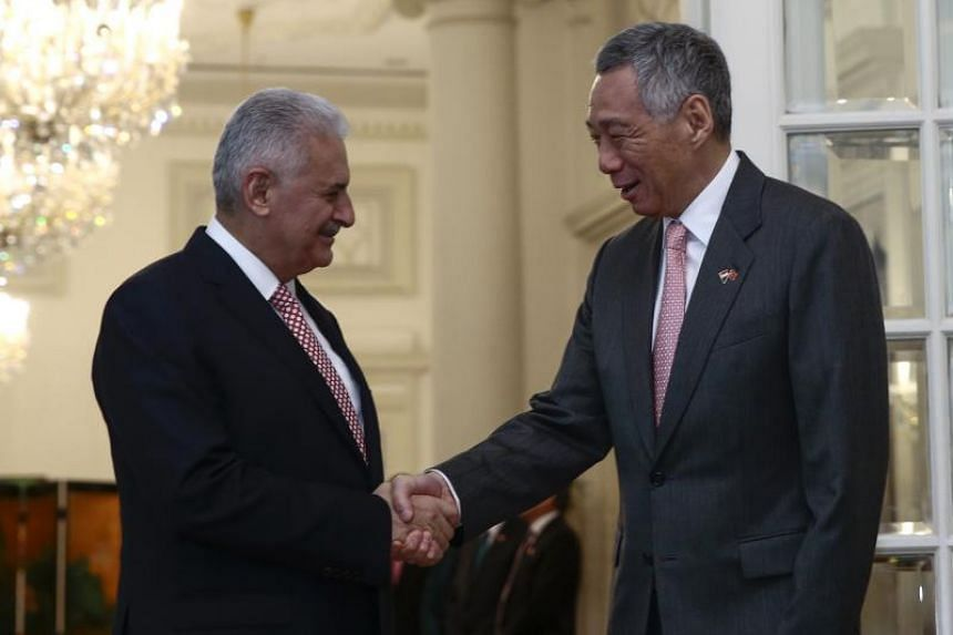 Turkish Prime Minister Binali Yildirim (left) and Singapore's Prime Minister Lee Hsien Loong (right) shake hands at the Istana Presidential Palace in Singapore on Aug 21, 2017.