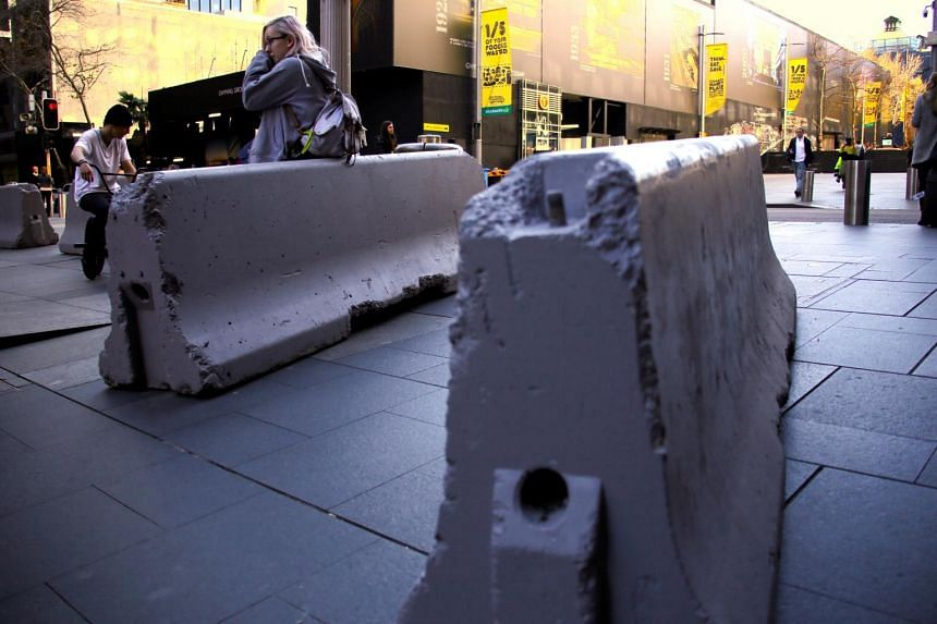 A woman resting on one of many concrete blocks that have been placed by the authorities as an extra security measure at Martin Place in Sydney, Australia.
