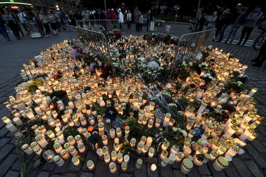 Candles and flowers at a makeshift memorial for the victims at Turku's market square, where the attack happened on Aug 18, 2017.