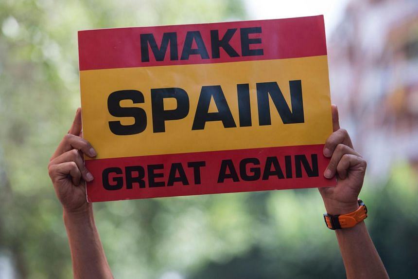 A demonstrator holds a banner during an anti-independence demonstration outside the Guardia Civil quarters in Barcelona on July 31, 2017.