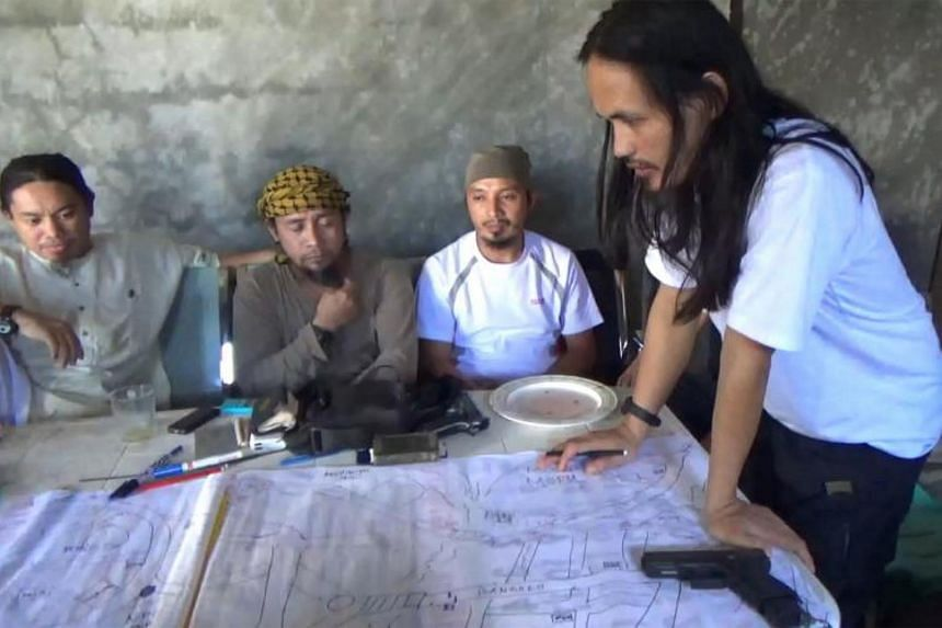 This screengrab taken from a video released by the Philippine Army on June 18, 2017, shows Abdullah Maute (right) looking at an improvised map of Marawi, while Isnilon Hapilon (second from left), leader of hardline group Abu Sayyaf looks on, as they