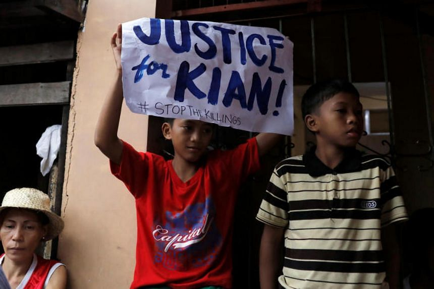 A school boy holds up a placard at the wake of Kian Loyd delos Santos, a 17-year-old high school student, who was among the people shot dead last week in an escalation of President Rodrigo Duterte's war on drugs in Caloocan city, Metro Manila on Aug