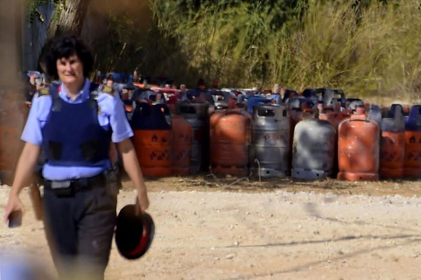 A policewoman walks with dozen of gas bottles in background in Alcanar during a search linked to the Barcelona and Cambrils attacks on the site of an explosion.
