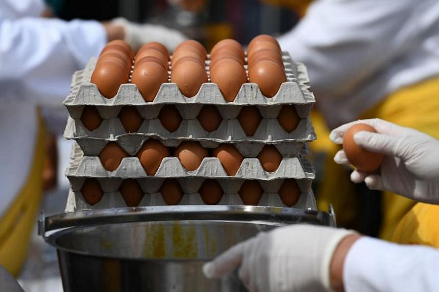 Members of the World Brotherhood of the Huge Omelet crack eggs to create a 6500 egg omelet on Aug 15, 2017 in Malmedy.