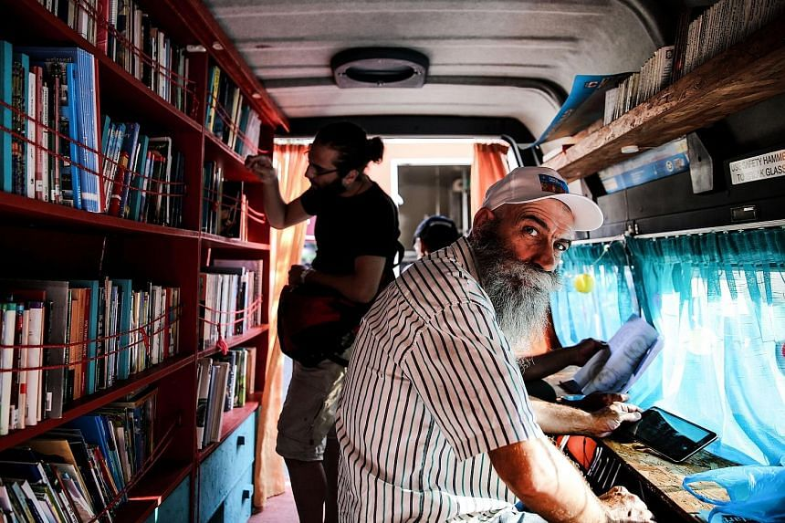 A minivan fitted with shelves of books in Athens, Greece, allows visitors to browse books.
