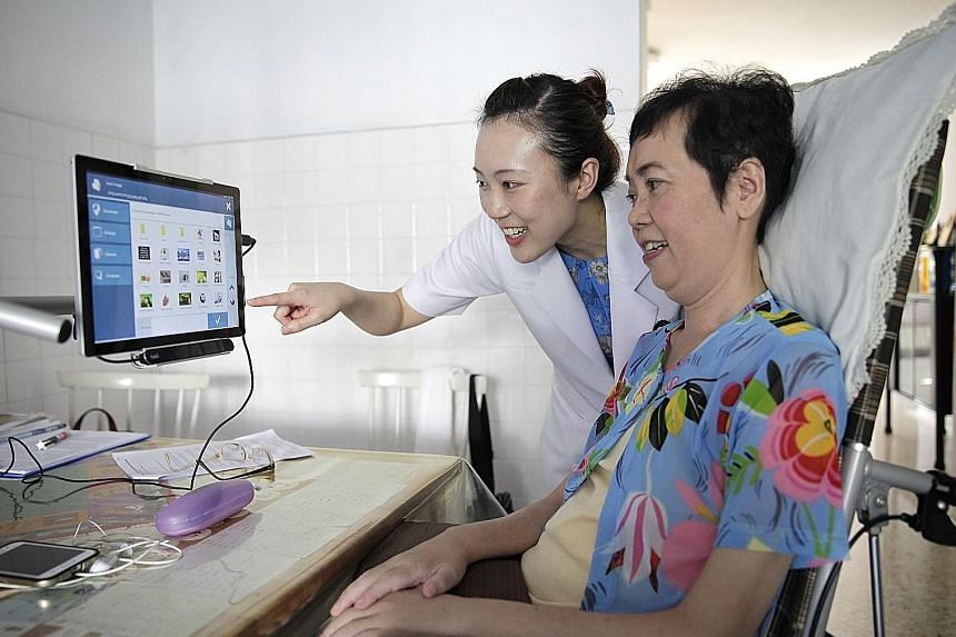TTSH speech therapist Tan Xuet Ying shows Ms Sharon Teo how to use an eye-gaze device that allows her to communicate via a computer. Ms Teo has a progressive neuro- degenerative disease known as Amyotrophic lateral sclerosis.