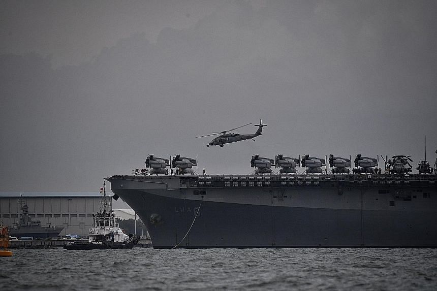 Above: The amphibious assault ship USS America, which is now in Changi, will provide messing and berthing services to the crew of the USS John S. McCain and support damage control efforts on board, the US 7th Fleet said late yesterday. Below: The USS