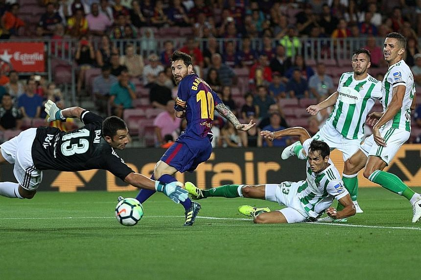Barcelona skipper for the day Lionel Messi scoring his side's first goal past Real Betis goalkeeper Antonio Adan in their La Liga opener, a 2-0 win at the Nou Camp on Sunday. Last season's runners-up, playing for the first time after the terror attac