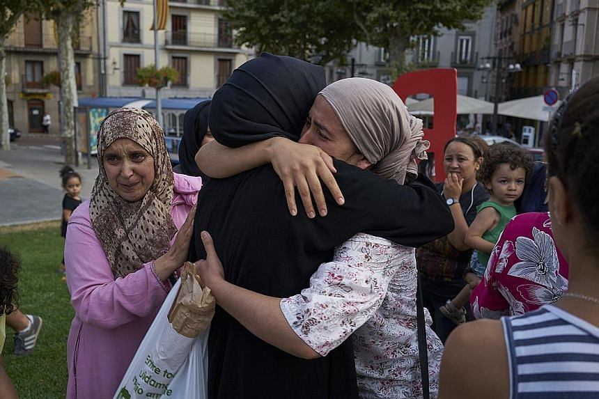Relatives of the men suspected to be behind the Barcelona and Cambrils attacks gathering with other Muslims in the main square of Ripoll, a town close to the French border, last Saturday. Younes Abouyaaqoub's mother Hannou Ghanimi had appealed on the week
