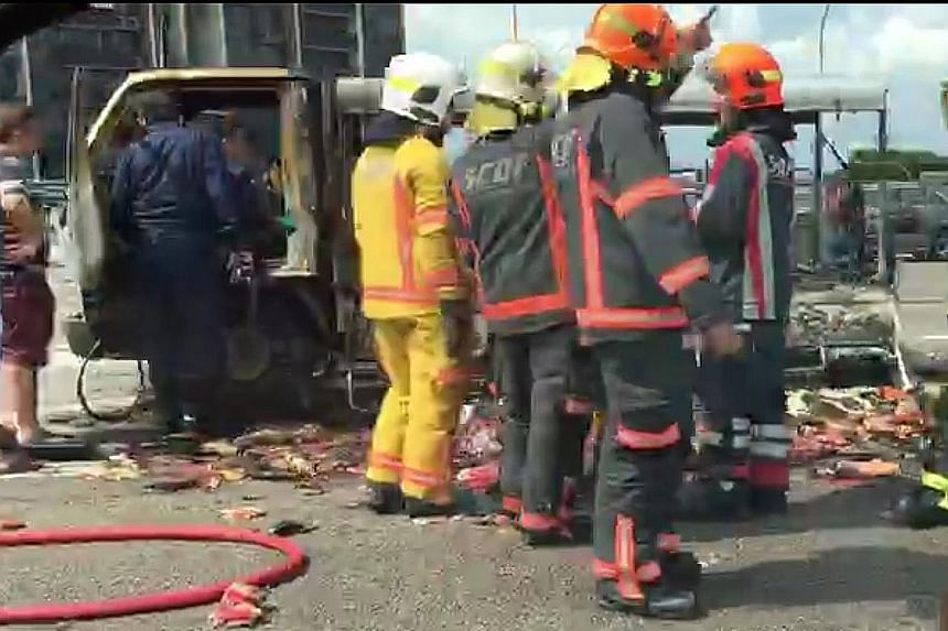 SCDF firefighters checking the partially-charred lorry. No one was hurt in the incident on the Pan-Island Expressway.