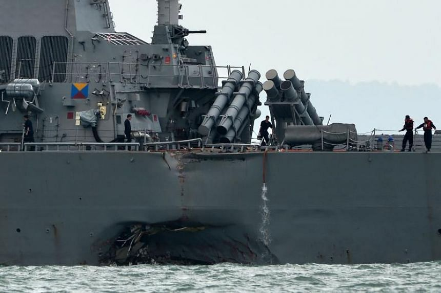 The guided-missile destroyer USS John S. McCain is seen with a hole on its portside after a collision with an oil tanker outside Changi Naval Base in Singapore on August 21, 2017.