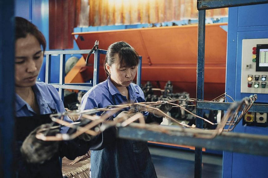 Workers check the work of a welding robot at a PQI Industrial Technology Group, which opened an US$18 million factory in Shenyang, China, on June 29, 2017.