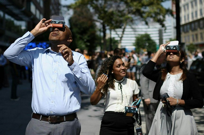 People step outside their workplace to look up at the partial solar eclipse in downtown Washington, on Aug 21, 2017.