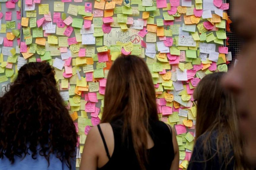 People look at notes with tributes to the terrorist attack victims pinned to a wall at the La Rambla, in Barcelona, Spain on Aug 19, 2017.