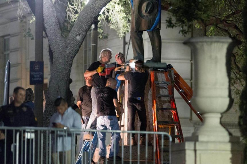 Workers remove Confederate Postmaster General John Reagan statue from the south mall of the University of Texas in Austin, Texas, US on Aug 21, 2017.