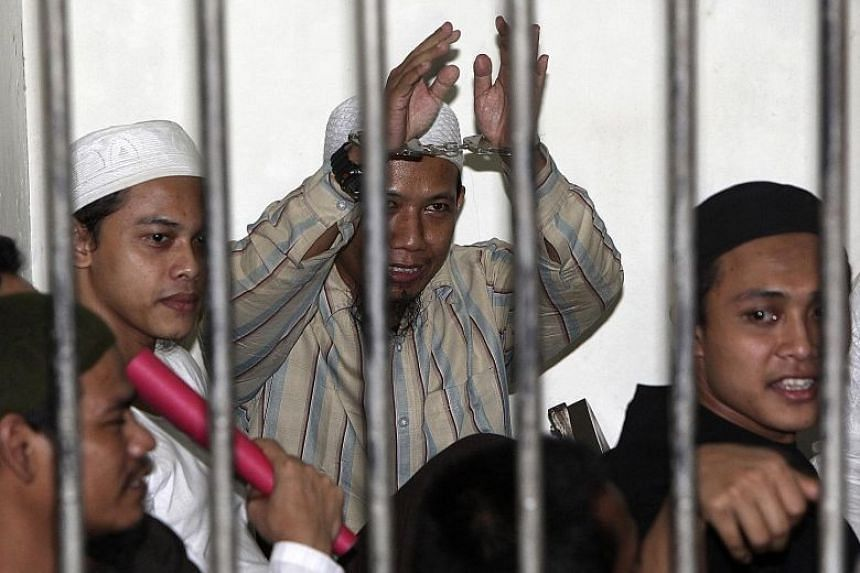ISIS-linked cleric Aman Abdurrahman (hands raised) in a holding cell in Jakarta awaiting trial in 2010.