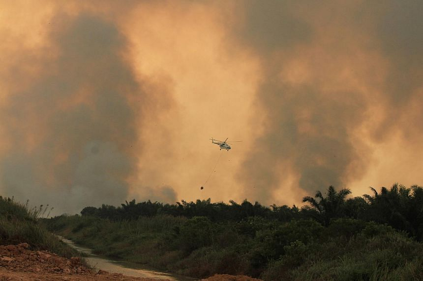 A helicopter operated by the Indonesian National Disaster Management Agency conducting water bomb operations to put out fires in Ogan Ilir, South Sumatra, on Aug 6, 2017.