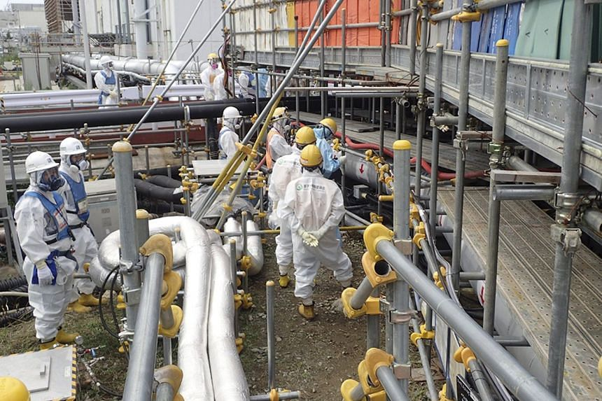 TEPCO workers injecting coolant liquid in the ground around the crippled Fukushima Daiichi Nuclear Power Plant in Okuma, Fukushima prefecture, on Aug 22, 2017.