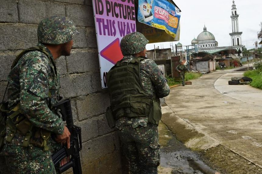 Philippine Marines watching a colleague walk away from a house on July 22, 2017, as they take cover from sniper fire while on patrol at the frontline in Marawi, as fighting between government troops and Islamist militants continues.