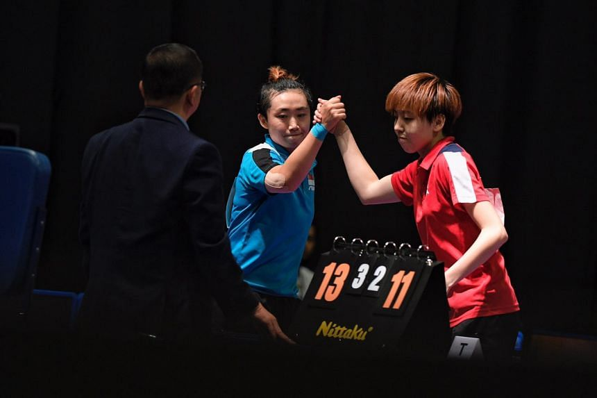 Singapore's Feng Tianwei (left) and Zhou Yihan shaking hands after their finals match, on Aug 22, 2017.