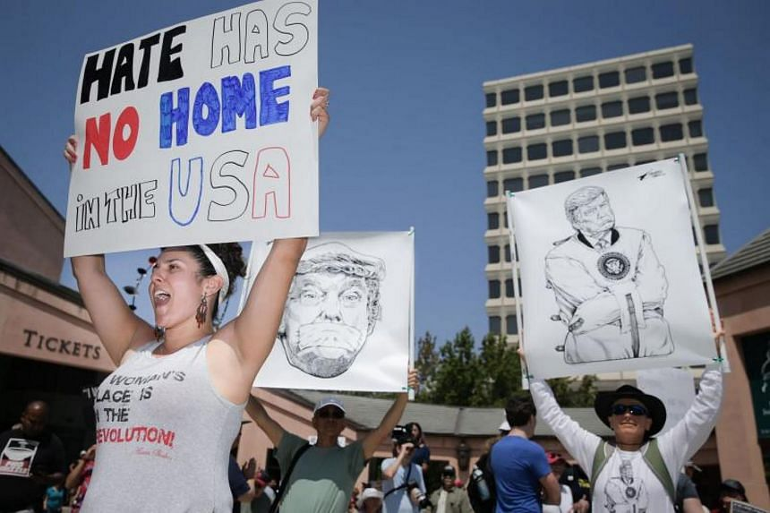 Natalia Price (left) of San Jose, holds an anti-hate sign at a rally against white nationalism on Aug19, 2017 in Mountain View, California.