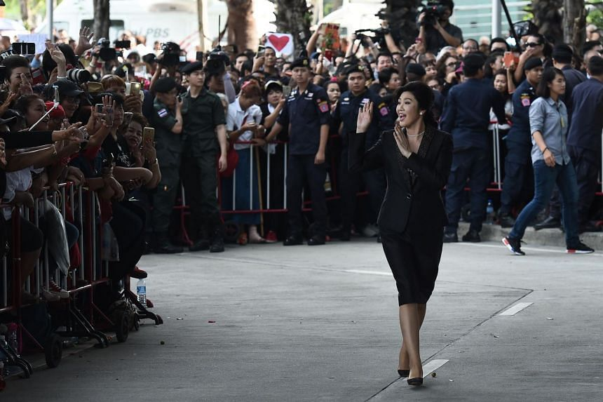 Former Thai prime minister Yingluck Shinawatra waves to supporters as she arrives at the Supreme Court in Bangkok.