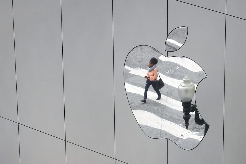 A woman is reflected in a Apple store logo in San Francisco.