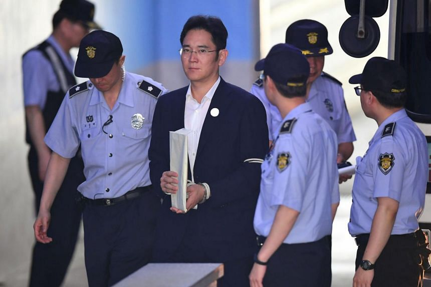 Lee Jae Yong (centre) being escorted by prison guards as he arrives at the Seoul Central District Court.