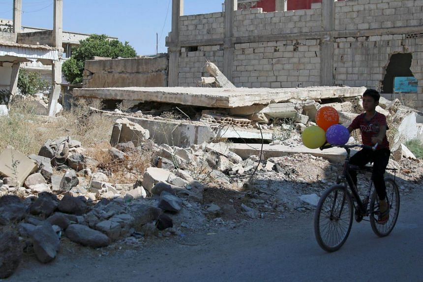 A boy rides a bike along a damaged street in a rebel-held area, in the town of Dael, Syria, on Aug 22, 2017.