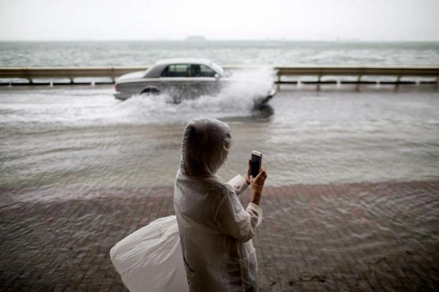 A woman takes pictures of passing cars on a flooded street as typhoon Hato passes by in Hong Kong, China on Aug 23,2017.