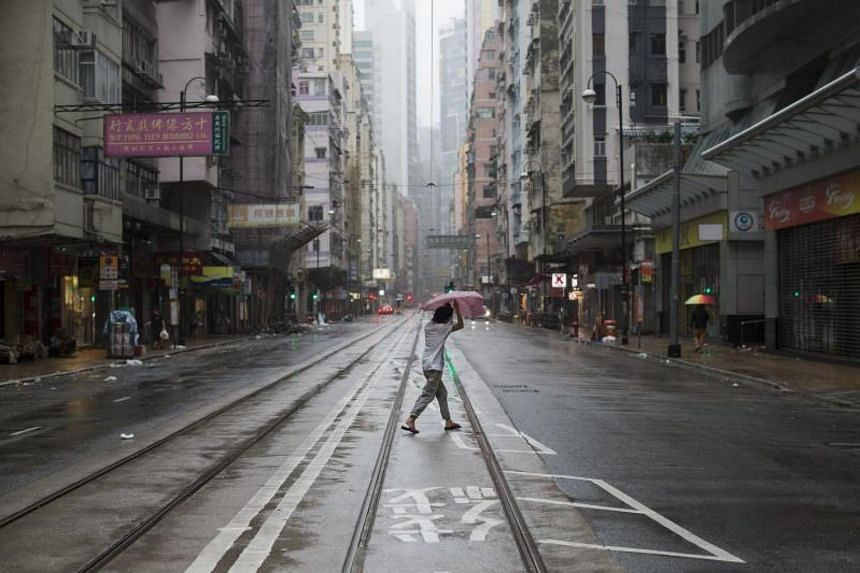 A woman crosses an empty street as typhoon Hato passes by in Hong Kong, China on Aug 23, 2017.