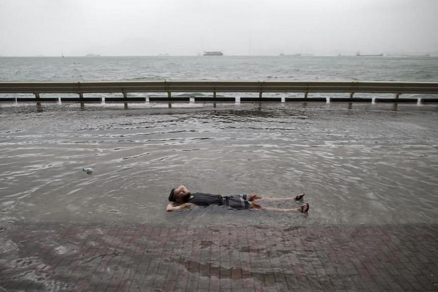 British citizen and Hong Kong resident Mark Mooney lies on a flooded street as typhoon Hato passes by in Hong Kong, China on Aug 23, 2017.