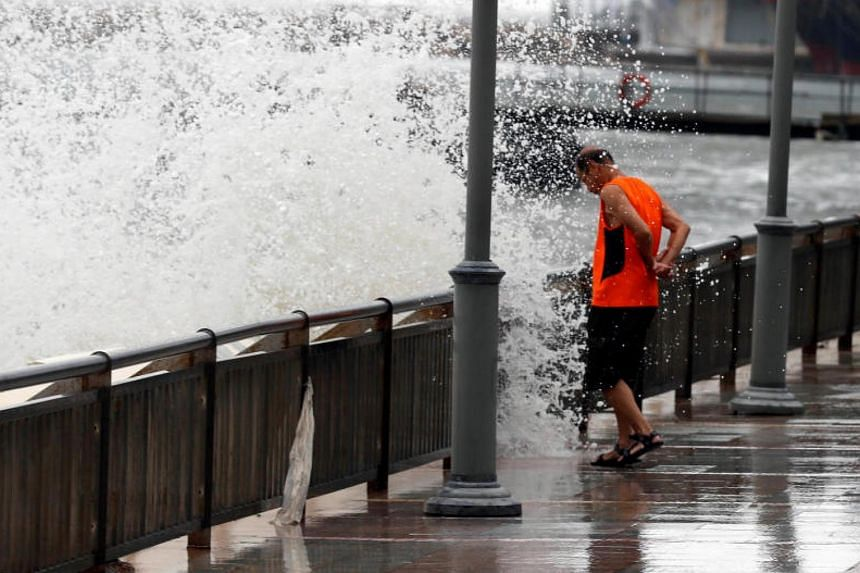 A man reacts after a big wave on a waterfront as Typhoon Hato hits Hong Kong, China on Aug23, 2017.