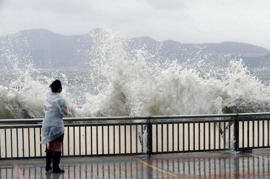 A woman stands beside a big wave on a waterfront Typhoon Hato hitting in Hong Kong, China on Aug 23, 2017.