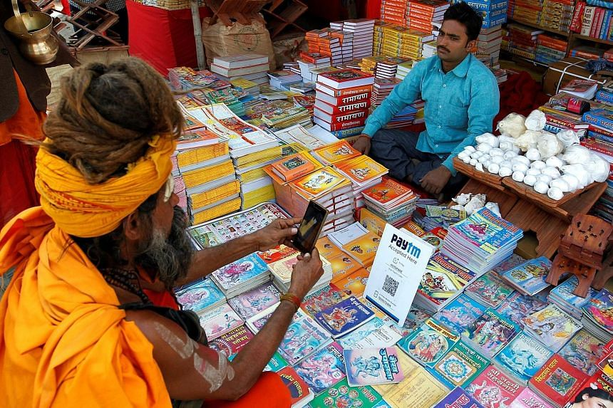 """A man paying for a book via electronic payment system Paytm in Allahabad, in Uttar Pradesh. India shows strong potential for digital payments and is categorised as a """"breakout"""" nation in the Digital Evolution Index 2017."""