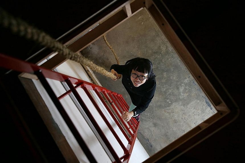 Artist Debbie Ding under a trapdoor that leads to her work in the basement.