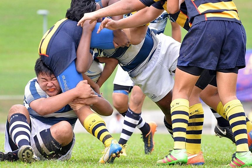 St Andrew's Secondary School players trying to stop the charge of Anglo-Chinese School (Independent) during the Schools National C Division rugby final[…], which the latter won 25-10.