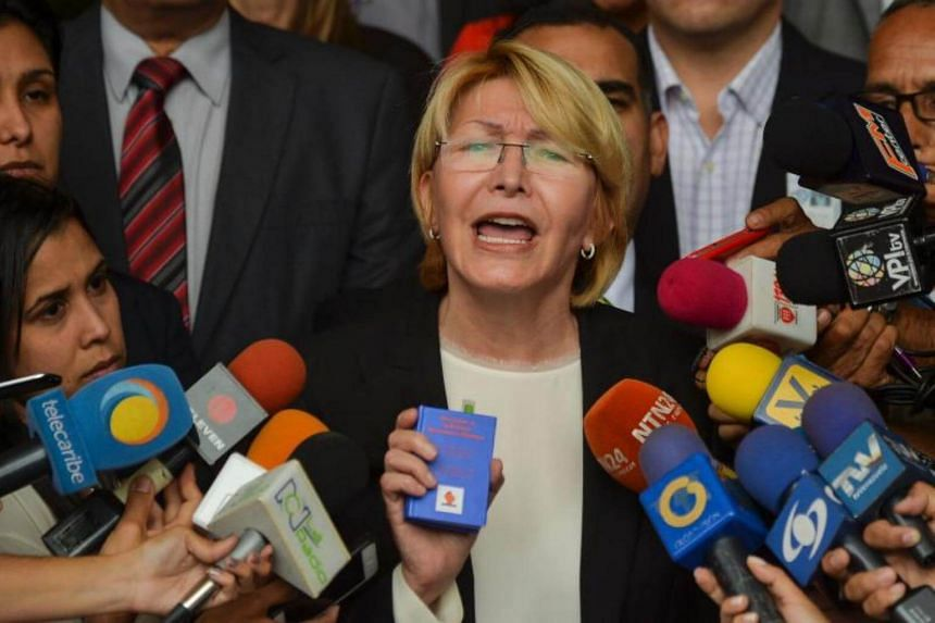 Venezuela's Attorney General Luisa Ortega holding a copy of the constitution while giving a press conference outside the Supreme Court of Justice in Caracas on June 8, 2017.