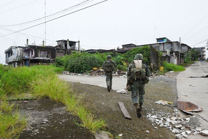 Philippine troops patrolling a deserted neighbourhood in Marawi last month. Dozens of militants remain holed up in the city.