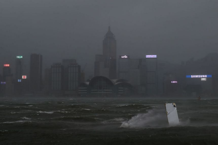 A piece of debris (right) carried by winds from Typhoon Hato is blown across Victoria harbour as dark skies hover over the Hong Kong island skyline, on Aug 23, 2017.
