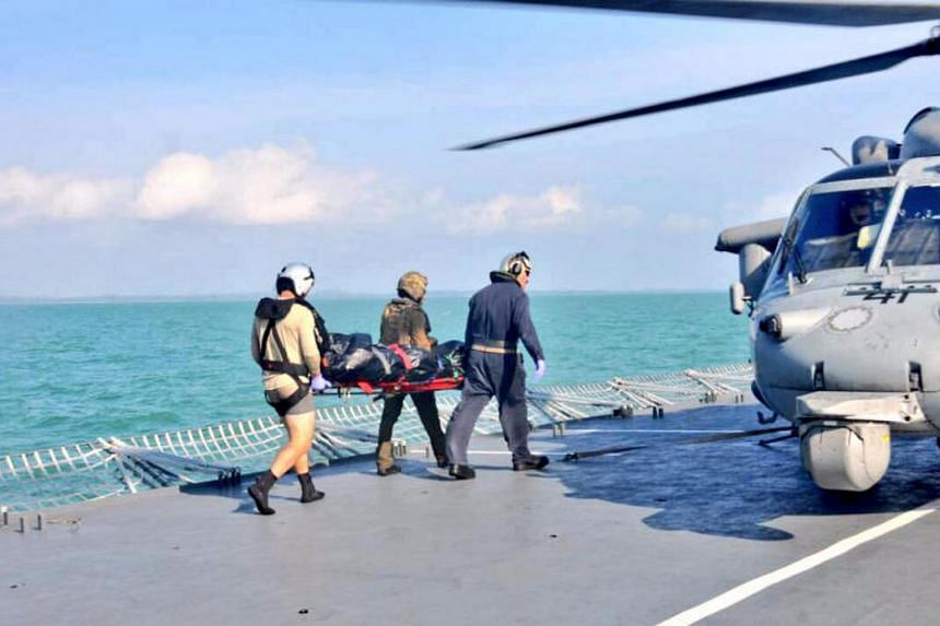 Royal Malaysian Navy personnel carry a body onto a U.S. Navy helicopter from USS America during a search and rescue operation for survivors of the USS John S. McCain ship collision in Malaysian waters on Aug 23, 2017.