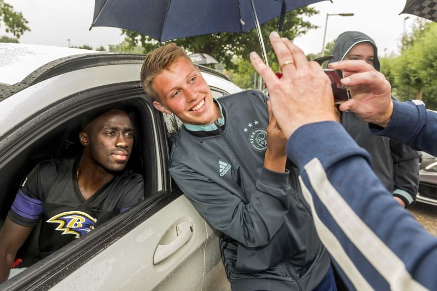 Sanchez (left) poses in his car for a selfie with a fan in Amsterdam.
