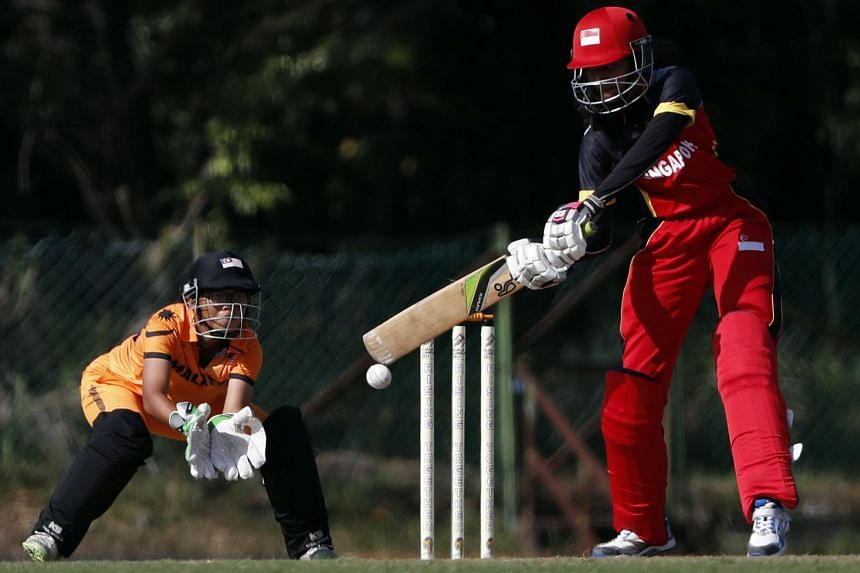 Singapore's Roshni Ramesh, who was 11 not out, in the women's SEA Games T20 cricket match against Malaysia on Aug 23, 2017, as wicket-keeper Emylia Eliani keeps watch.