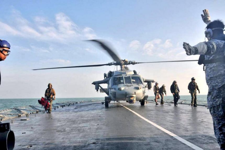 A US Navy helicopter from USS America lands on Royal Malaysia Navy's KD Lekiu Frigate 30 during a search and rescue operation for survivors of the USS John S. McCain ship collision in Malaysian waters on Aug 23, 2017.