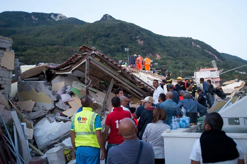 Italian firemen and emergency workers search through rubble of a collapsed house in Ischia on Aug 22, 2017.