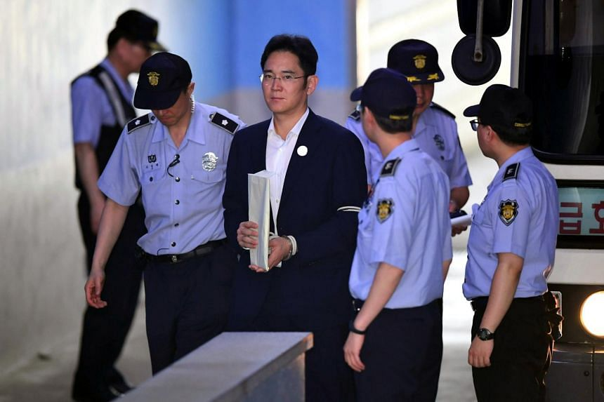 Lee Jae Yong (centre), the vice-chairman of Samsung Electronics, is escorted by prison guards as he arrives at the Seoul Central District Court.