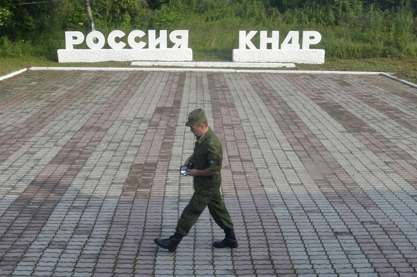"""A guard walks past signs reading """"Russia"""" (left) and """"DPRK"""", in Tumangan, North Korea."""